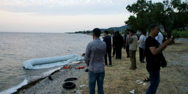Syrian migrants gather next to their destroyed dinghy after their arrival from Turkish coasts at a Mytilene...