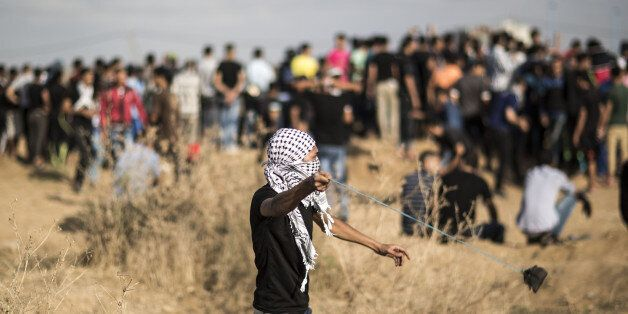 GAZA STRIP, Oct. 9, 2015-- A Palestinian protester hurls stones at Israeli troops during clashes near...