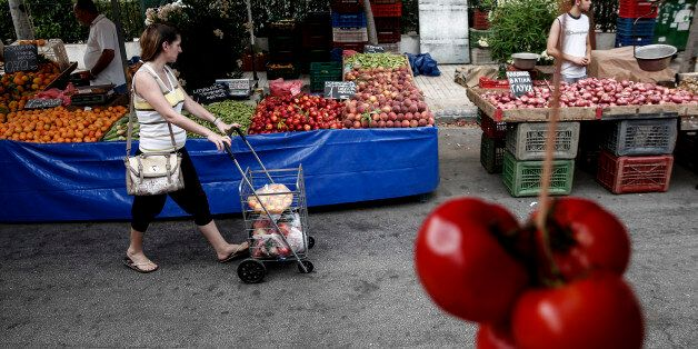 A customer pushes her shopping cart between food stalls at an open air street market in Athens, Greece,...