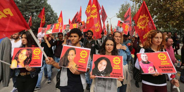 Protesters carrying pictures of people killed in Saturday's bombing attacks, walk during a march in Ankara,...