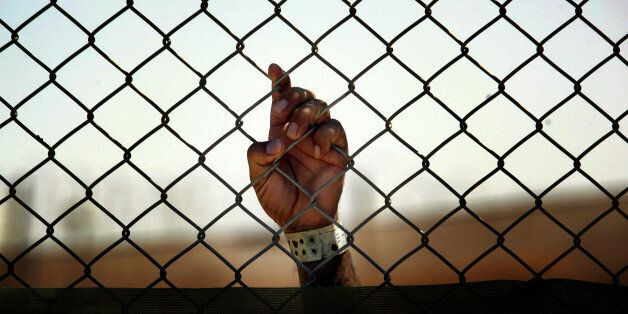 An Iraqi detainee holds onto a fence enclosing him at the Camp Cropper detention centre, located in Baghdad,...
