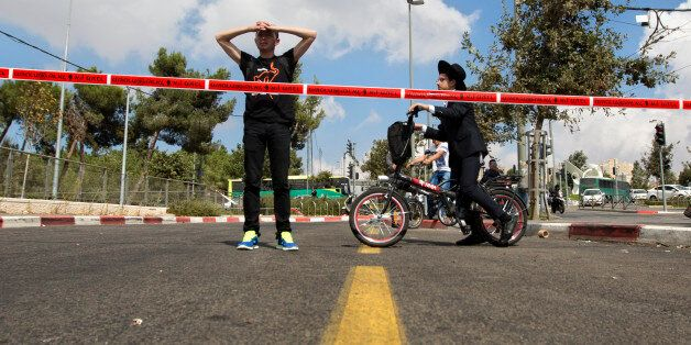 Israelis look at the scene of a stabbing attack in Jerusalem, Thursday, Oct. 8, 2015. A Palestinian stabbed...