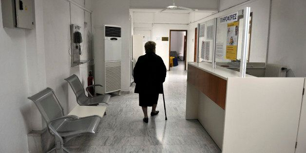 A woman walks a closed branch Greek state health fund EOPYY in an Athens suburb on February 17, 2014,...