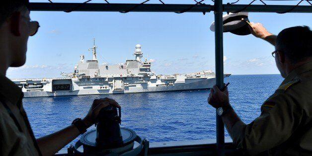 The commander (R) Stefan Klatt of German navy frigate ship Werra salutes the Italian navy carrier Cavour...