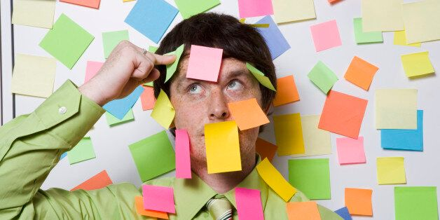 Male office worker covered with sticky notes