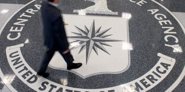 A man crosses the Central Intelligence Agency (CIA) logo in the lobby of CIA Headquarters in Langley,...