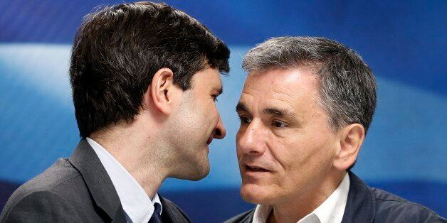 Greek Finance Minister Giorgos Houliarakis, left, chats with outgoing Finance Minister Euclid Tsakalotos...