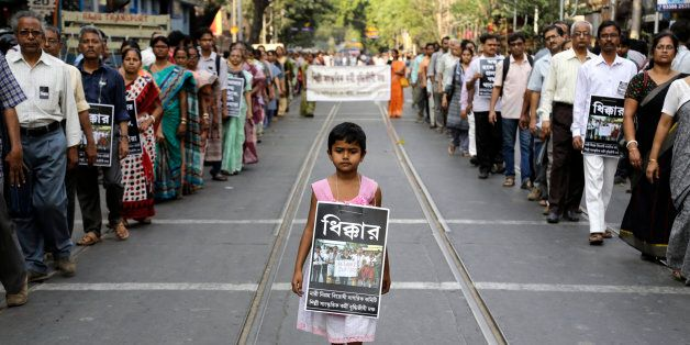 A girl walks with others in a silent procession protesting the gang rape of a nun at a convent at Ranaghat,...