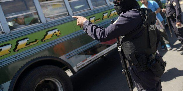 National Civil Police officers stand guard at a bus terminal in San Salvador on July 30, 2015 during...