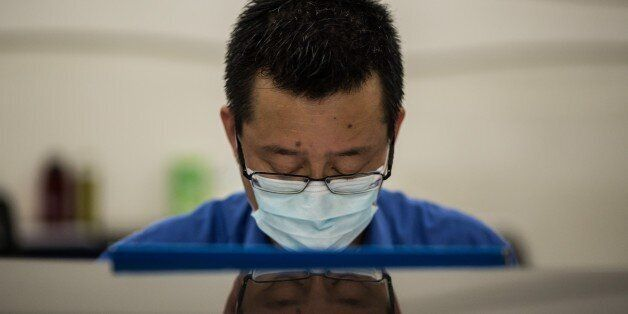 A member of staff wears a face mask at Kowloon station in Hong Kong on June 27, 2015, after a 17-year-old...