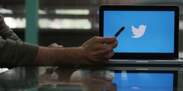 An Apple Inc. iPhone 6 smartphone is held as a laptop screen shows the Twitter Inc. logo in this arranged...