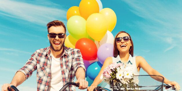 Low angle view of cheerful young couple smiling and riding on bicycles with colorful balloons in the