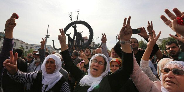 Protesters flash the V-sign as they protest Saturday's bombing attacks, during a rally in Ankara, Turkey,...