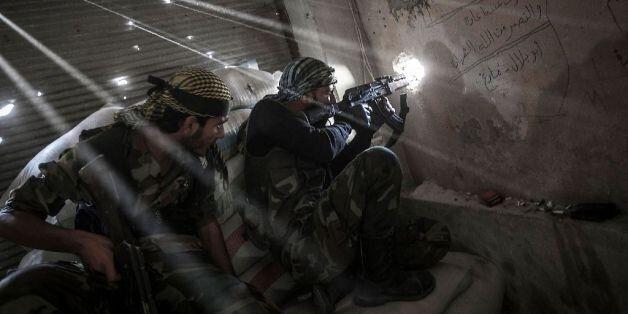 October 21, 2012 - Aleppo, Syria USA: Rebel fighters belonging to the Javata Harria Sham Qatebee watch...