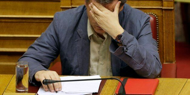 Greece's Finance Minister Euclid Tsakalotos reads his notes during a parliament meeting in Athens, Wednesday,...
