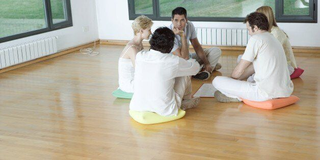 Group therapy session, adults sitting in circle on floor,
