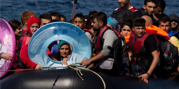 Refugees and migrants arrive on a dinghy after they crossed from Turkey to Lesbos island, Greece, Friday,...