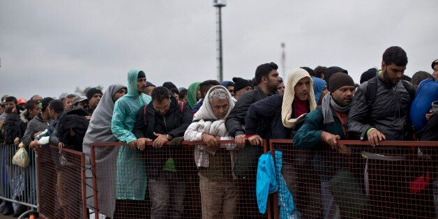 People queue in order to get inside a reception center for migrants and refugees in Opatovac, Croatia,...