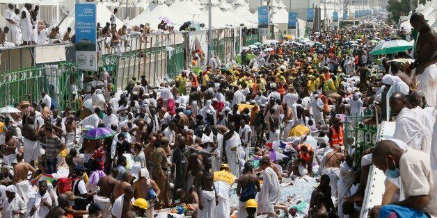 Muslim pilgrims and rescuers gather around people who were crushed by overcrowding in Mina, Saudi Arabia...