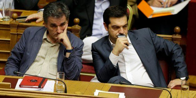 Greece's Prime Minister Alexis Tsipras, right, and Finance Minister Euclid Tsakalotos attend a parliament...