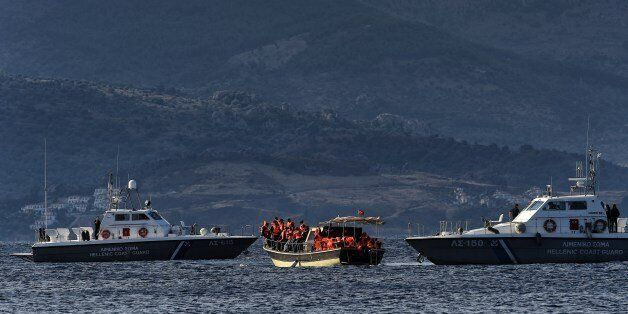 A boat carrying refugees and migrants stops between two Hellenic coast guard boats near the Greek island...