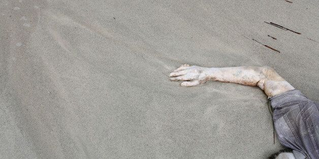 In this Monday, Sept. 7, 2015 photo, the body of a drowned man lies on the beach west of the town of...