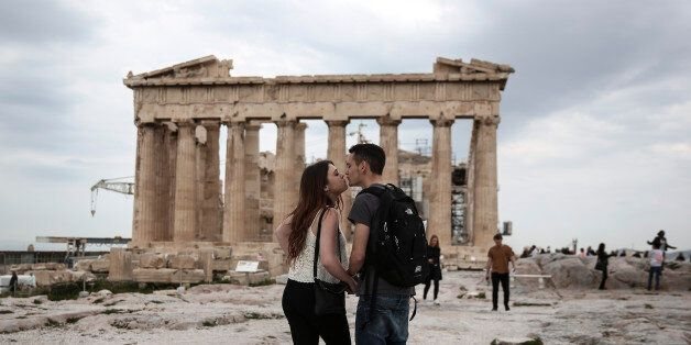 U.S. visitors Zach Branch,19, right, and Madison Franklin, 18, both from California, kiss in front of...