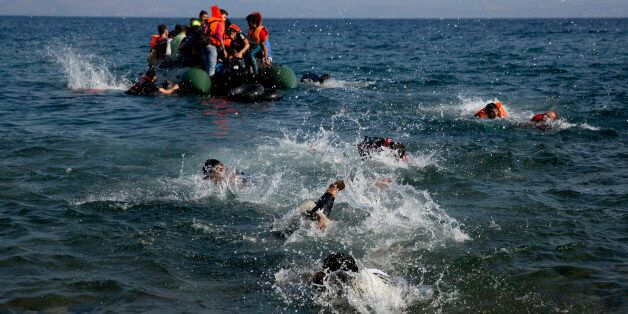 Migrant whose boat stalled at sea while crossing from Turkey to Greece swim to approach the shore of...