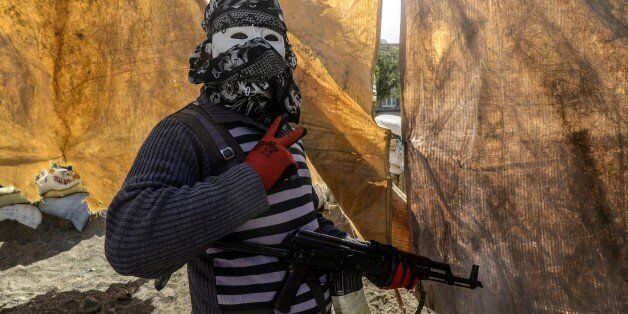 An armed Kurdish militant of the Kurdistan Workers' Party (PKK) wearing a mask and a scarf covering his...