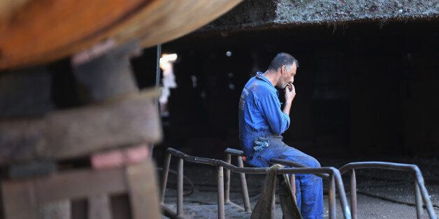 ATHENS, GREECE - JULY 08: A shipyard worker takes a break as he works on the hull of a new ship being...