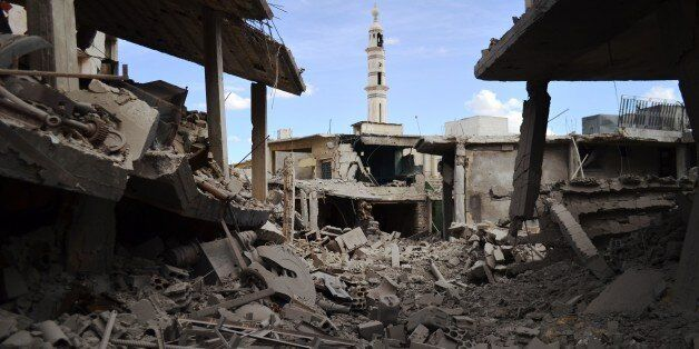 A picture taken on September 30, 2015 shows damaged buildings and a minaret in the central Syrian town...