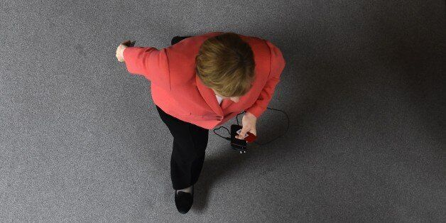 German Chancellor Angela Merkel walks through the plenary hall to vote on a new Greece bail-out deal...