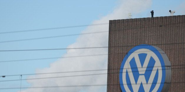 A man looks through binoculars as he stands next to a corporate logo of Volkswagen on the rooftop of...