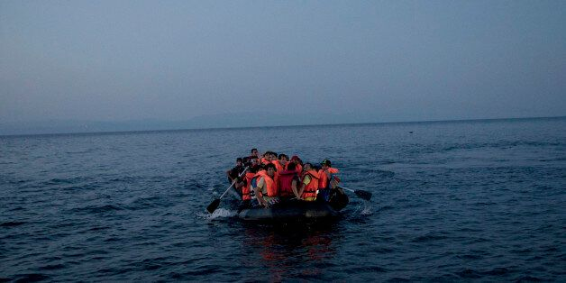 Syrian refugees arrive aboard a dinghy after crossing from Turkey, to the island of Lesbos, Greece, on...