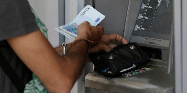A man uses an ATM of a bank after the government's decision last week to limit daily cash withdrawals...