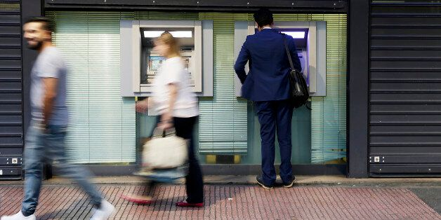 A customer operates an automated teller machine (ATM) beneath metal shutters in Athens, Greece, on Thursday,...