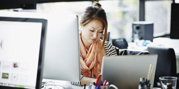 Businesswoman sitting at desk in high tech startup office working on