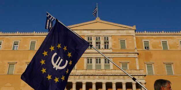 A pro-Euro demonstrator holds a European Union flag in front of Greek Parliament during a rally at Syntagma...