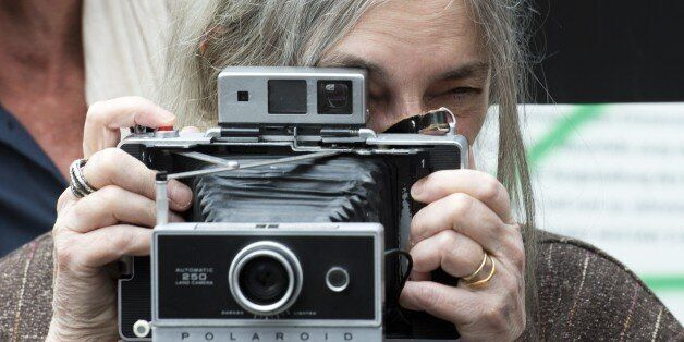 US singer-songwriter Patti Smith poses with her camera in front of a stretch of the Berlin wall on May...