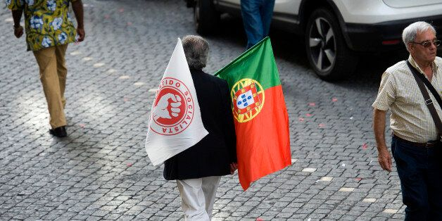 A supporter of Antonio Costa, leader of the Socialist party, holds flags during the final round of campaigning...