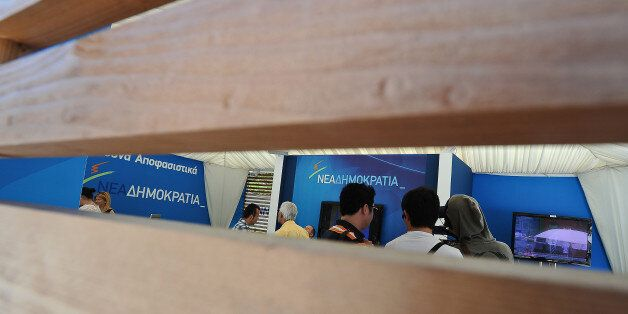 People walk inside a New Democracy conservative party election campaign kiosk near the Greek Parliament,...