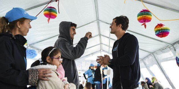 British actor and UNICEF Goodwill Ambassador Orlando Bloom (R) smiles as he speaks with a Syrian refugee...