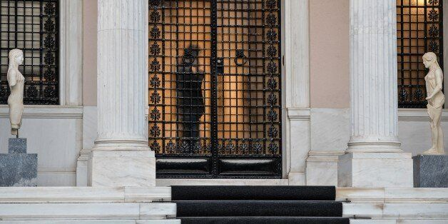 A person is seen through the glass door of the Maximou' palace which houses the offices of the Greek...