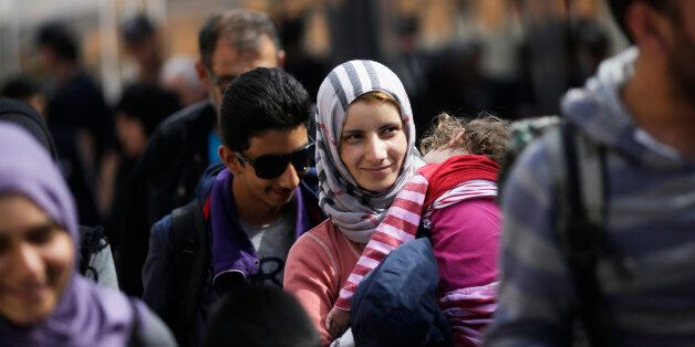 A woman with a baby, saying they are from Syria, arrives with other refugees at the train station of...