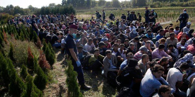A group of migrants sits and waits to be escorted to a train after crossing a border from Croatia near...