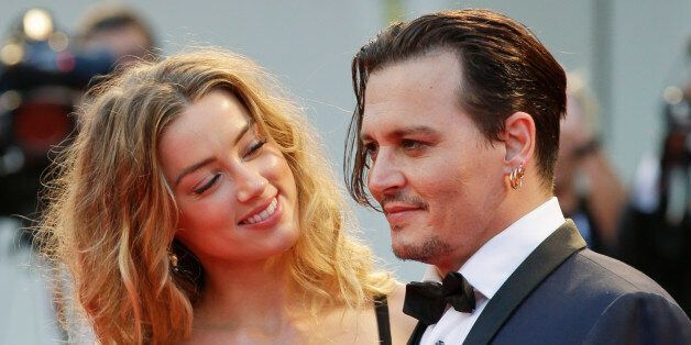 Amber Heard, left, and Johnny Depp pose for photographers upon arrival at the premiere of the film Black...