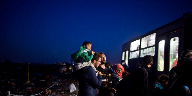 A Syrian refugee child sits on his father's shoulder as they wait to get on a bus that will take them...