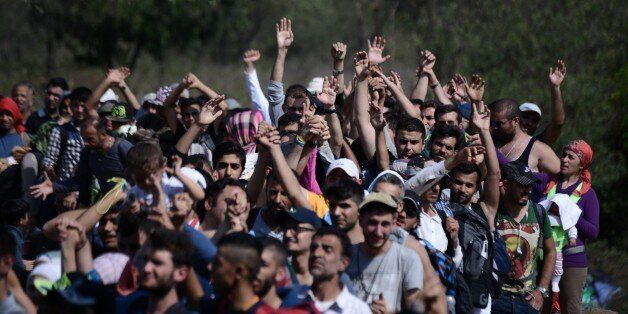Refugees and migrants raise their hands in order to be allowed by the Macedonian police to cross the...
