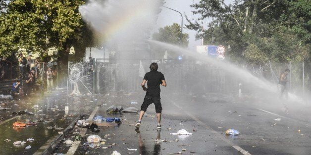 A man stands opposite Hungarian riot police using water cannon to push back refugees at the Hungarian...