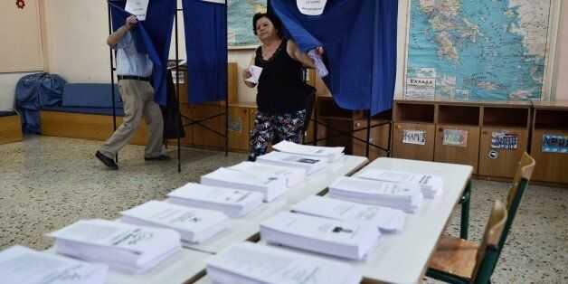 A woman exits a polling booth prior to cast her ballot in central Athens on September 20, 2015. Over...